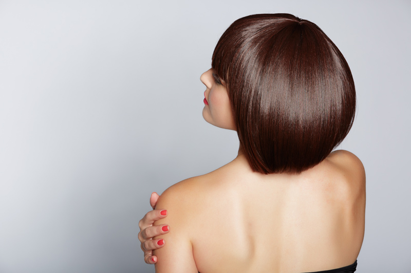 Woman wearing shiny wig cut into sophisticated bob.